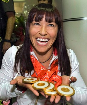 Chantal Petitclerc, winner of five gold medals at the 2008 Paralympics in Beijing, is shown showing her medals as she arrives at Trudeau airport in Montreal Friday, Sept. 19, 2008. Petitclerc has been named as a new senator. THE CANADIAN PRESS/Ryan Remiorz