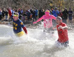 Owen Sound Mayor Ian Boddy, left, bounds into the freezing water with Darcy King and unidentified pink man at the 2016 Polar Plunge for Special Olympics in Owen Sound. (James Masters/ The Sun Times, Owen Sound)