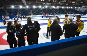 Referees speak to team South Korea as Team Japan looks on during the seventh draw at the women's world curling championships in Swift Current, Sask., on March 21, 2016. (THE CANADIAN PRESS/Jonathan Hayward)