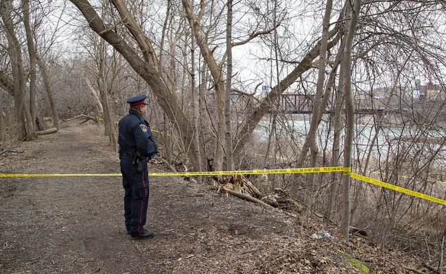 A Brantford Police officer stands watch on Tuesday March 22, 2016 on a trail on the west side of the Grand River, just south of the Lorne Bridge in Brantford, Ontario. Human remains were found by a passerby late Monday evening and staff for the Centre for Forensics Science in Toronto will assist to gather evidence and identify the body. The area is expected to remain cordoned off until late Tuesday. Brian Thompson/Brantford Expositor/Postmedia Network