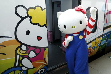 A performer dressed as a Hello Kitty poses next to Hello Kitty-themed Taroko Express train in Taipei, Taiwan March 21, 2016. The train will make its inaugural run on a round trip from Taipei to Taitung on Monday, according to the Taiwan Railways Administration (TRA). REUTERS/Tyrone Siu