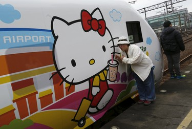Fans pose next to Hello Kitty-themed Taroko Express train in Taipei, Taiwan March 21, 2016. The train will make its inaugural run on a round trip from Taipei to Taitung on Monday, according to the Taiwan Railways Administration (TRA). REUTERS/Tyrone Siu