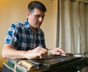 Dale Rivard of Tilbury plays a pedal steel guitar at the London home of guitar maker Bent Romnes. (MIKE HENSEN, The London Free Press)