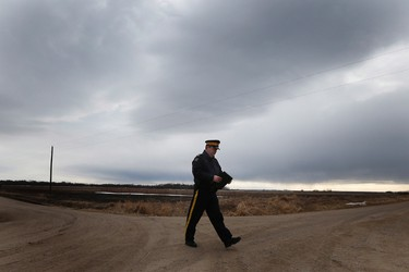 RCMP Sgt. Bert Paquet walks across a country road to update media on the discovery of two-year-old Chase Martens' body in a creek close to his home just north of Austin, Manitoba on Saturday, March 26, 2016. Martens went missing from his family home Tuesday evening. THE CANADIAN PRESS/John Woods