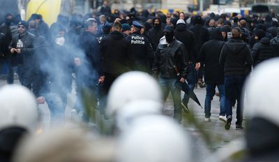 Police attempt to disperse right wing demonstrators as they protest near one of the memorials to the victims of the recent Brussels attacks, at the Place de la Bourse in Brussels, Sunday, March, 27, 2016. (AP Photo/Alastair Grant)