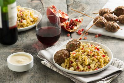 <b>MIDDLE EASTERN POMEGRANATE AND TAHINI PASTA SALAD WITH LAMB KEBABS</b>(Courtesy of Executive Chef Renée Bellefeuille, Art Gallery of Ontario, Toronto)<br><br><b>Ingredients:</b><br> 4 cups (1 L) water<br> 1/4 tsp. (.5mL) salt<br> 1 pkg (375 g) fusilli pasta<br> 3 Tbsp. (45 mL)extra-virgin olive oil<br> Juice of one lemon<br> <b>Tahini Dressing</b> <br> 1/2 cup (125mL) tahini <br> 1/4 cup (60 ml)warm water<br> Zest of one lemon<br> 1/4 tsp. (.5mL)salt<br> Fresh cracked black pepper to taste<br> 1 tsp. (5mL) ground cumin<br> <b>Garnish:</b><br> 1/4 cup (60mL) pomegranate seeds<br> 1 cup (250mL) fresh crumbled cauliflower florets<br> 1/4 cup (60mL) finely diced red onion<br> 2 Tbsp. (30mL) lightly toasted sesame seeds<br> 1/4 cup (60mL) finely chopped Italian flat leaf parsley<br> <b>Lamb Kebabs</b><br> 1 lb (500 g)ground lamb<br> 2 Tbsp. (30mL) finely diced red onion<br> 1/4 cup (60mL) finely chopped Italian flat leaf parsley<br> 1 egg<br> 2 tsp. (10mL) ground cumin<br> 1 tsp. (5 mL) coriander<br> 1/4 tsp. (.5mL)chilli flakes<br> Salt and pepper to taste<br> 8 skewers<br><br> <b>Method</b><p> <b>Pasta:</b>  Bring water to a rapid boil. Add salt and pasta and stir until water returns to boil. Cook fusilli for 7 minutes to tender. Drain and toss pasta with extra virgin oil and lemon juice while warm, then spread on tray to cool. </p> <p><b>Tahini Dressing:</b><p>Using a medium size mixing bowl, add warm water slowly to tahini, whisking until smooth and water is completely incorporated. Then add lemon zest, salt, pepper and cumin. Set aside. When pasta is cool, transfer it to a large bowl and combine with tahini dressing, pomegranate seeds, cauliflower, onions, sesame seeds and parsley, tossing until evenly mixed. Pasta will be served cool.</p><p> <b>Lamb Kebabs:</b><p> Preheat oven to 400F (200C). Combine all ingredients in a bowl and mix thoroughly. Separate mixture into 8 evenly sized balls. Mould each ball around tip of a skewer, flattening into a 2-inch oval. Rep