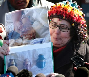 Jennifer Neville-Lake holds pictures of her children Harry and Millie holding hands in hospital before they died outside the Newmarket court on March 29, 2016 where Marco Muzzo was just sentenced for a drunk-driving crash that claimed their lives. (Craig Robertson/Toronto Sun/Postmedia Network)
