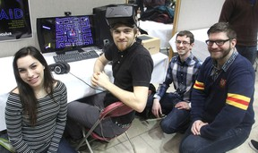 Queen's University students, from left, Brianna Rubin, Jonathan Stanford, Graham McGregor and Daniel Clarke gather around their virtual reality version of Pac-Man at a showcase of computer science at Queen's University on March 31. (Michael Lea/The Whig-Standard)