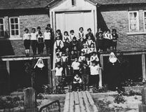 Native children and nuns are seen in front of a residential school in Maliotenam, Que., circa 1950. (Library Archives of Canada)
