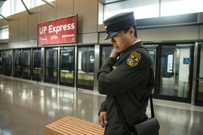 A uniformed employee listens to his radio on the platform at Pearson Airport with Toronto's UP Express in the background. Craig Robertson/Toronto Sun/Postmedia Network