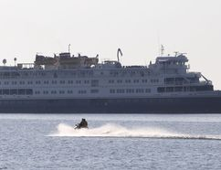 A personal watercraft passes the Great Lakes cruise ship M.S. Saint Laurent while it was moored off Kingston, Ont. on Tuesday July 28, 2015. Great Lakes cruise ships are becoming more common, and Sarnia Mayor Mike Bradley believes his city should become a port of call. Elliot Ferguson/Kingston Whig-Standard/Postmedia Network
