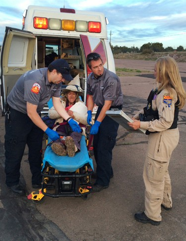 """This photo taken, Saturday, April 9, 2016, and provided by Arizona Department of Public Safety shows an ambulance taking Ann Rodgers, 72 , to safety after she was lost in the forest for nine days. Rodgers got lost in the White Mountains in eastern Arizona after her hybrid car ran out of gas and battery on March 31. Rodgers survived in the forest for nine days by drinking pond water and eating plants. Authorities came across her dog April 9, and a DPS flight crew spotted a """"help"""" signal made of sticks and rocks on the ground. Rodgers had left the area, but she was found on a reservation that's home to the White Mountain Apache Tribe after starting a signal fire.  (Arizona Department of Public Safety via AP)"""
