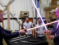 Britain's Prince William, right, and Prince Harry use light sabres during a tour of the Star Wars sets at Pinewood studios in Iver Heath, west London, Tuesday April 19, 2016. Prince William and Prince Harry toured Pinewood to visit the production workshops and meet the creative teams working behind the scenes on the Star Wars films. (Adrian Dennis/Pool via AP)