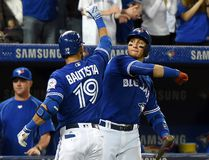 Toronto Blue Jays right fielder Jose Bautista is greeted by shortstop Troy Tulowitzki after hitting a two run home run against Oakland Athletics at Rogers Centre. (Dan Hamilton/USA TODAY Sports)