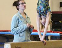 Fort Gymnastics Club head coach Leanne Cameron, pictured above training a student, says her club is the only sports organization in town that has to find and fund their own building. (File photo)