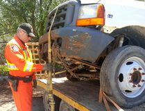Const. Ron Tricker, with the Chatham-Kent Police Service traffic unit, checks to see if this vehicle has been safely secured to a trailer during a commercial vehicle safety blitz on Wednesday, April 27, 2016 in Chatham, Ont. conducted in partnership with the Chatham-Kent OPP and Ministry of Transportation. Of the 27 vehicles inspected, 13 were taken out of service, one was impounded and six licence plates were seized. (Handout/Chatham Daily News)