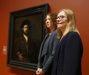 Jan Allen, director of the Agnes Etherington Art Centre at Queen's University, right, and Jacquelyn Coutre, curator of the Bader Collection, stand with the gallery's newest addition, Rembrandt van Rijn's 1658 painting Portrait of a Man with Arms Akimbo on Thursday in Kingston. The masterpiece, donated late last year by Alfred and Isabel Bader, is to be unveiled Friday at the gallery's spring and summer season launch. (Elliot Ferguson/The Whig-Standard/Postmedia Network