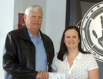 Wallaceburg Sports Hall of Fame's Tom Ayres donates $1,500 to Wallaceburg District Secondary School athletic director Janine Day. The money will go towards the renovation of the school's new fitness centre. An anonymous WDSS alumnus donated $1,000, with the Sports Hall of Fame kicking in another $500.
