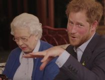 """This image taken from a video released by Kensington Palace, London, on Friday April 29, 2016 shows Queen Elizabeth II sitting with her grandson, Prince Harry as he says """"Boom"""" whilst receiving a video call from the President of the United States, Barack Obama and Michelle Obama. Prince Harry, released the video Friday promoting the upcoming Invictus Games for wounded veterans. The cast includes his grandmother Queen Elizabeth II, and Barack and Michelle Obama, who Harry had over for dinner last week. The video starts with Harry and the queen looking at an Invictus brochure when they get a video phone message from Mrs. Obama. (@KENSINGTONROYAL via AP)"""