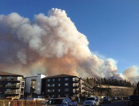 Smoke from a wildfire fills the sky in downtown Fort McMurray looking southeast on Sunday, May 1, 2016. An out-of-control wildfire has forced about 700 people from their homes near Fort McMurray in northern Alberta. (Greg Halinda/The Canadian Press)