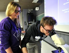 Postgraduate Emily Kyle (left) observes high school student Chad Sawyer as he peers through a microscope at Western University in London Ont. May 3, 2016. CHRIS MONTANINI\LONDONER\POSTMEDIA NETWORK