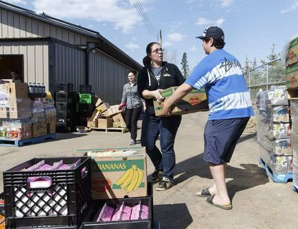 Anzac Grocery owner Candace Strugess (left) and volunteer Joseph Whelan, 15, work to move supplies at the store in Anzac, Alta., on Wednesday May 4, 2016. A massive evacuation of Fort McMurray was held after a large wildfire struck the city. IAN KUCERAK / POSTMEDIA