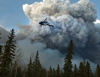 A helicopter flies past a wildfire in Fort McMurray, Alta., on Wednesday May 4, 2016. THE CANADIAN PRESS/Jason Franson