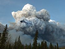 A helicopter flies past a wildfire in Fort McMurray