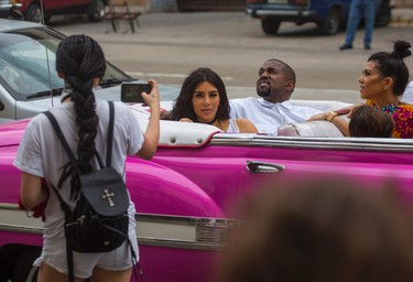 A woman uses her cellphone to take a picture American reality-show star Kim Kardashian West, center, and her husband Kanye West as they ride on a classic car along the streets of Havana, Cuba, Wednesday, May 4, 2016. Rap superstar Kayne West, his wife Kim Kardashian and members of her reality-show-star family have become the latest celebrities to visit Havana. They visited Havana's Museum of Rum Wednesday, stepping out of a hot-pink antique American convertible as they snapped selfies and were recorded by a television crew following them around. At right is Kourtney Mary Kardashian. (AP Photo/Desmond Boylan)