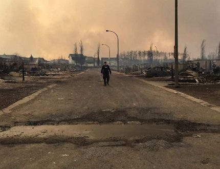 A Mountie surveys the damage on a street in Fort McMurray. Alberta RCMP