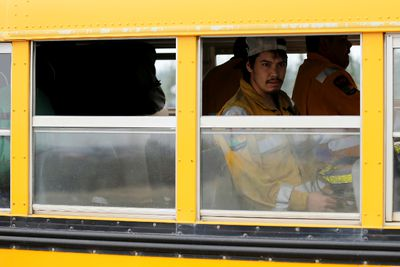 Firefighters arrive on a bus to help battle wildfires near Fort McMurray, Alberta, Canada, May 5, 2016. REUTERS/Chris Wattie