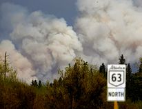 FORT MCMURRAY, ALBERTA: MAY 5, 2016 - Plumes of smoke rise above the trees near Fort McMurray on May 5, 2016. An out-of-control wildfire covering over 10,000 hectares of forest has forced the evacuation of Fort McMurray, the fourth largest city in Alberta. Over 80,000 residents of the northern Alberta city have been evacuated as fire threatens to consume the city and surrounding area. A provincial state of emergency has been declared in Alberta.