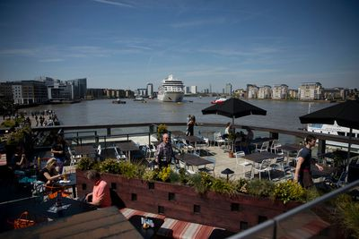 People look out from a restaurant roof terrace as the Viking Sea cruise ship docks at Greenwich in London, Thursday, May 5, 2016. The vessel, owned by Viking Sea, arrived in London Thursday for its naming ceremony in Greenwich where it will be the largest ocean ship to be christened on the River Thames. (AP Photo/Matt Dunham)