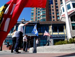 Russell Webb, left, and other members of Bytown Brigantine raise flags during grand opening ceremonies for the Aquatarium tourism attraction in this file photo from May. (FILE PHOTO)
