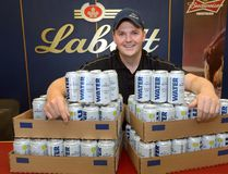 Brewmaster Cory Kummer shows off some of the 69,000 cans of drinking water Labatt is donating to evacuees and firefighters in wildfire-ravaged Fort McMurray, Alta. The brewer has another 131,000-plus cans ready to ship if needed. (MORRIS LAMONT, The London Free Press)