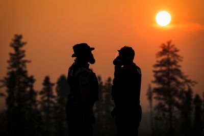 Two RCMP police officers wear gas masks in the smoke from the wildfires near Fort McMurray, Alberta, Canada, May 6, 2016. REUTERS/Mark Blinch