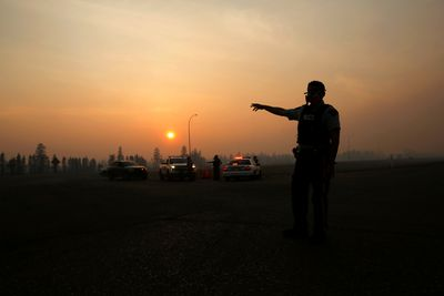 A police officer wears a mask to protect himself from smoke from the wildfires as he directs traffic near Fort McMurray, Alberta, Canada, May 6, 2016.  REUTERS/Mark Blinch