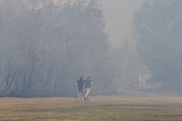 Nearby residents run through smoke caused by a forest fire near Wolf Willow in Edmonton, Alta., on Sunday, May 8, 2016. (CODIE MCLACHLAN PHOTO)