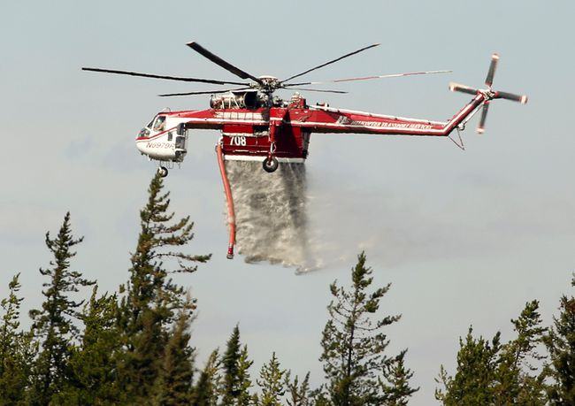 A helicopter battles a wildfire south of Fort McMurray, Alberta on May 8, 2016. PHOTO BY LARRY WONG