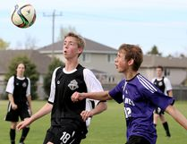 Tilbury Titans' David Brooks-Taylor, left, and Chatham Christian Flames' Ben Woelke watch the ball during the second half of a LKSSAA 'A' senior boys soccer game Monday at Chatham Christian High School. (MARK MALONE/The Daily News)