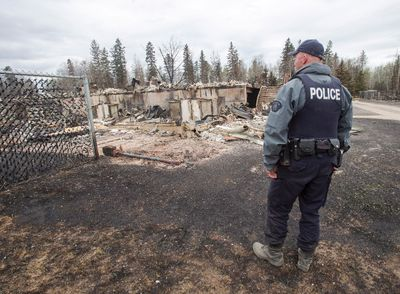 A police officer looks at the wildfire destruction in the Abasands neighbourhood in Fort McMurray Monday, May 9, 2016.THE CANADIAN PRESS/Ryan Remiorz