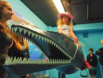 Aurora Foy is dressed to mosasaur-wrangle as she tries out the CFDC's recently unveiled Aquasaur Photo Booth. (Alexis Stockford/The Morden Times)