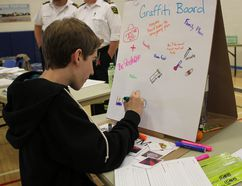 "Joey McRae draws a backpack on the Huron County Health Unit's ""Graffiti Board."" Students were asked to draw something they would need in case of emergency. (Laura Broadley/Goderich Signal Star)"