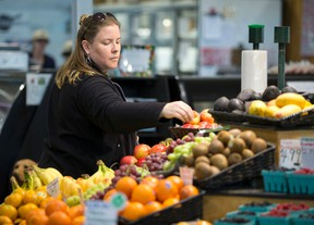 Angela Nadalin sorts through a basket of apples while shopping for fresh produce at The Doris Family Produce stand in the Covent Garden Market in London, Ont. on Wednesday May 11, 2016. (CRAIG GLOVER, The London Free Press)
