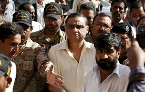 Police and Rangers soldiers escort Asim Hussain (C) into Sindh High Court in Karachi, Pakistan November 26, 2015. A Pakistani court ordered the prominent opposition politician close to former president Asif Ali Zardari into police custody on Thursday on charges of aiding terrorists in a case his party has called politically motivated. Hussain, a petroleum minister in the former Pakistan People's Party-led government, is accused of harbouring and providing medical treatment to militants and criminals at his hospital in the port city of Karachi.  REUTERS/Akhtar Soomro
