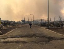 An RCMP officer surveys the damage of a street in Fort McMurray, Alta. on May 4, 2016. Reuters