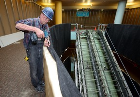 Supervisor Malcolm Pigott works Thursday near the Central Library?s escalator, which will be replaced with a stairway. A design rendering of the stairs, minus furnishings and colour choices, is shown at right. (MORRIS LAMONT, The London Free Press)