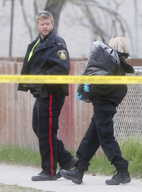 An animal control officer carries a garbage bag containing a dog that was, according to a witness, shot to death by police, in Winnipeg, last night.  Police arrived at 672 Wellington Ave., found a man shot in the chest, then they shot and killed his dog.   Friday, May 13, 2016.   Sun/Postmedia Network