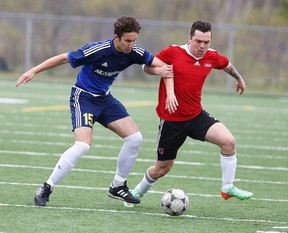 Luca Nardi of the  College Notre Dame Alouettes fights for the ball with Ryan Mooney of the St. Charles Cardinals during senior boys high school soccer action in Sudbury, Ont. on Thursday May 12, 2016. Gino Donato/Sudbury Star/Postmedia Network