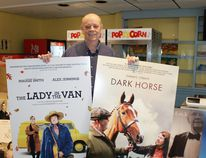Lambton Film and Food Festival chair Glen Starkey stands in the lobby of Forest's venerable Kineto Theatre, holding promotional posters of two of the nine films that will be shown during the four-day long annual festival. CARL HNATYSHYN/SARNIA THIS WEEK